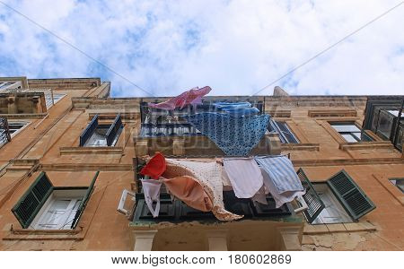 colorful clothes hanging on the line outside a balcony sandstone house with shutters view up into the sky