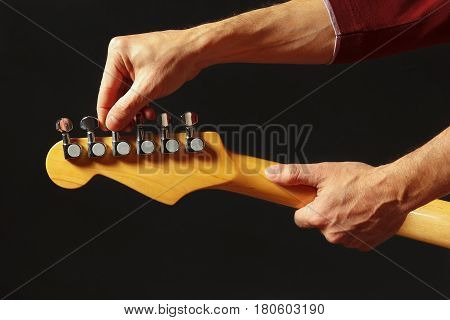 Hands of musician tunes the electric guitar on the black background