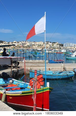 colorful traditional fishing boat with Maltese flag in Marsaxlokk Malta a fishers village