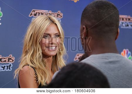 NEW YORK-AUG 11: Model Heidi Klum (L) speaks to TV personality AJ Calloway at the 'America's Got Talent' season 10 taping at Radio City Music Hall on August 11, 2015 in New York City.