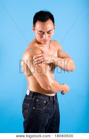Muscular man suffering from pain and discomfort on shoulder.