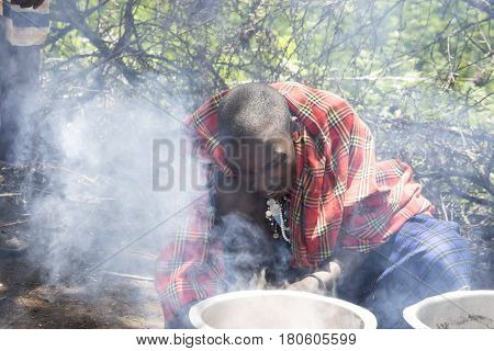 Maasi Man Cooking Ceremonial Meal, Ngorongoro Conservationa Area, Tanzania