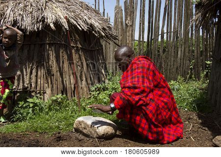 Chief Kneeling In Krall In Maasi Village, Ngorongoro Conservationa Area, Tanzania