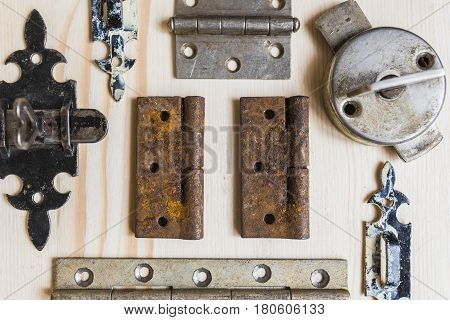 Old vintage locks and door hinges rusted and frayed with peeling paint spread out in order on a light wooden background