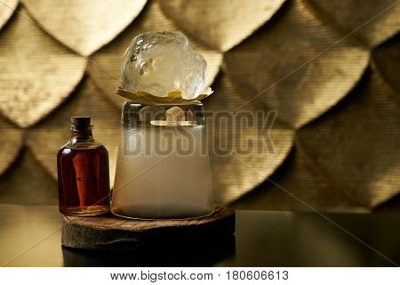 Close-up of a fresh branded alcoholic cocktail with ice and cognac and smoke in a Whiskey glass on a wooden birch bar counter. Concept of alcoholic and non-alcoholic bar beverage.