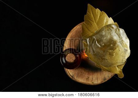 Close-up of a fresh branded alcoholic cocktail with ice and cognac and smoke in a Whiskey glass on a black birch bar counter. Concept of alcoholic and non-alcoholic bar beverage. Top view with copy space.
