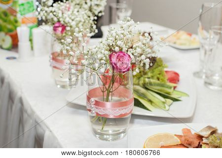 Jar with rose and baby's breath. Wedding decorations.