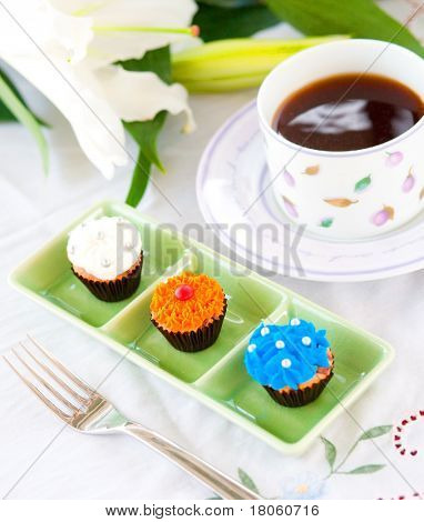 Three mini cupcakes with sugar frosting on green plate