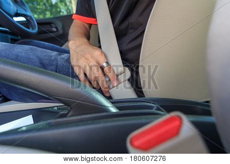 the man set the seat belt before drive the car.