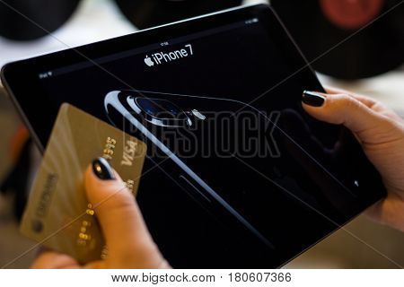 Moscow Russia 8 april 2017. Women hold visa gold card and use ipad for online shopping.