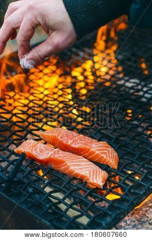 Grilled salmon steaks on a grill. Fire flame grill. Restaurant and garden kitchen. Garden party. Healthy dish. Raw meat and sunlight. Man hand keep and salt meat.