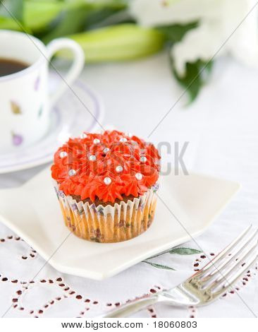 Pretty cupcake with red icing and silver balls