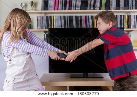 Siblings fighting desperately for the TV remote control in front of the television