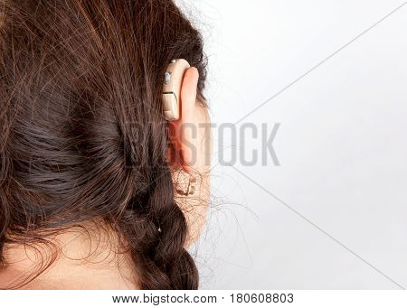 Close up of a woman's head and ear with hearing aid