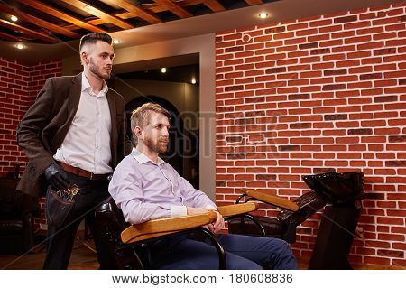 Hairdresser with barber tools standing near a man sitting on chair against brick wall. Interior of the modern barbershop. Two man. Master and client. Professionalism and craftsmanship.