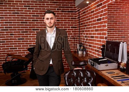 Young barber expert looking at camera and keeping hand on chair while standing at barbershop against brick wall. Portrait of hairdresser in the brown jacket. Horizontal photo. Mirror and barber tools. Professionalism and craftsmanship.