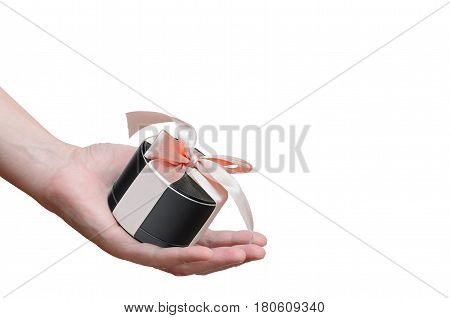 portable mobile speaker, tied with a pink ribbon in man's hand isolated on white background