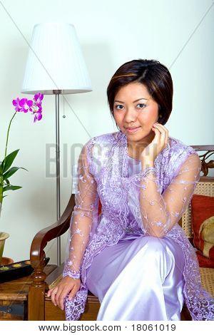 Bela mulher malaia Landim 'kebaya ' vestido e saia longa em um ambiente doméstico