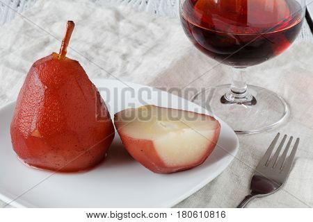 Pears poached in red wine sauce on white