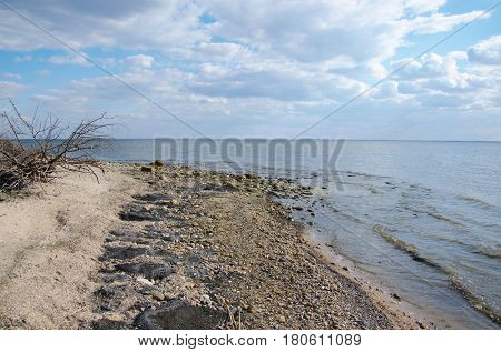 stones sticking out from water ashore lake