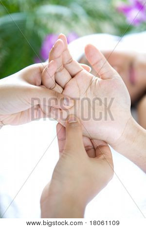 Woman receiving relaxing hand massage as part of beauty treatment poster