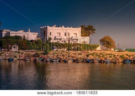 White Villa in Carthage, Tunisia. Landscape with sea, palms, boats, and arabic architecture.