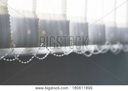 Vertical window blinds with sun light as a background.