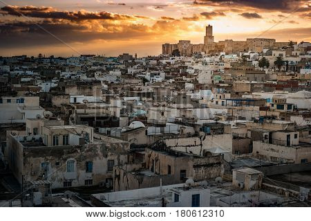 View of the Medina and the castle kasbah in Sousse, Tunisia. Cityscape of Sousse at dramatic sunset with red skies and clouds. poster