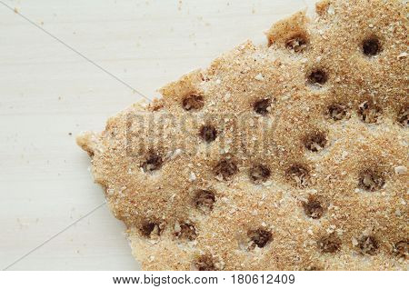 piece of a dry rye small loaf with crumbs on a wooden background healthy food concept