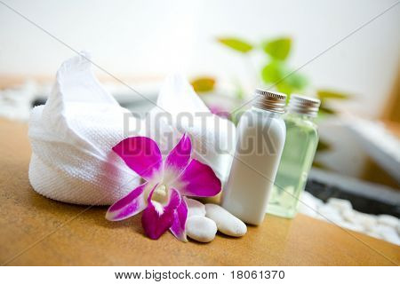 White towels, orchid and bath lotion in massage spa room poster