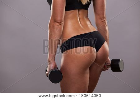 Athletic booty of girl with dumbbells isolated on grey background with copyspace.