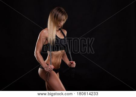 Beautiful fitness woman is holding a skipping rope. Sporty girl showing her well trained body. isolated on dark background with copyspace.