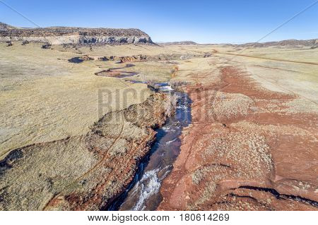 northern Colorado foothills aerial view with a creek, dam and cattle walk paths