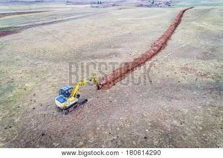 backhoe excavator digging an irrigation ditch at Colorado foothills - aerial view