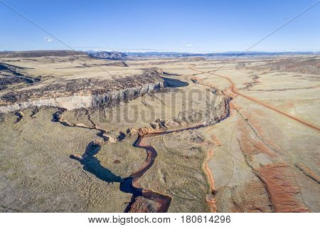 northern Colorado foothills aerial view with a creek, road and cattle walk paths