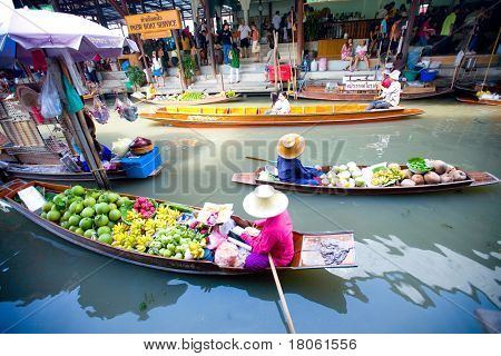 Bangkok August 2008. Busy sunday morning at Damnoen Saduak floating market. Locals selling fresh produce, cooked food and souvenirs while tourist waits of boats for hire.