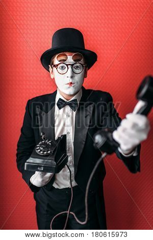 Mime theater actor performing with old telephone