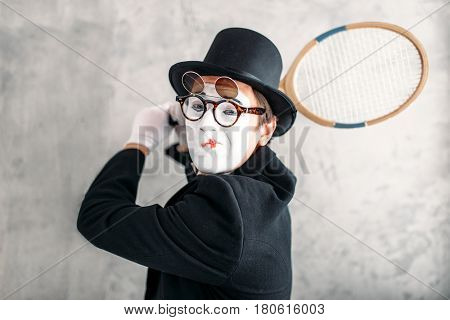 Pantomime actor performing with badminton racket