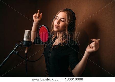 Woman vocalist in headphones against microphone
