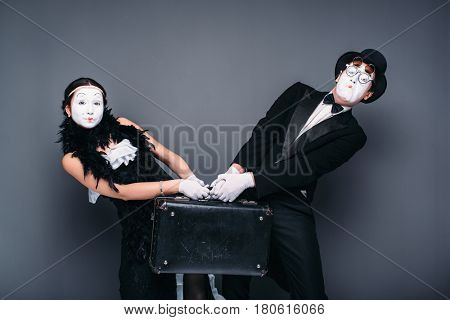 Mime actor and actress performing with suitcase