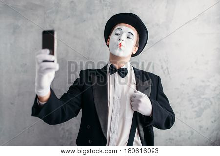 Pantomime actor with makeup mask makes selfie