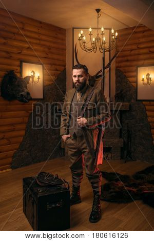 Hunter man with old gun against antique chest