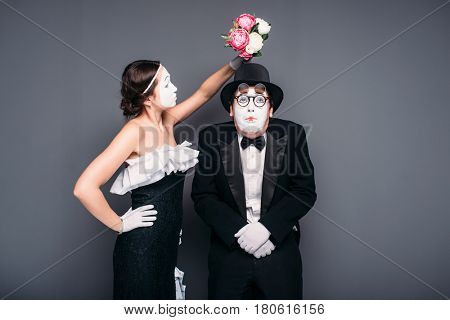 Comedy actor and actress poses with flower bouquet