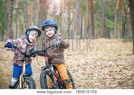 Two Little Siblings Having Fun On Bikes In Autumn Or Spring Forest. Selective Focus On Boy.