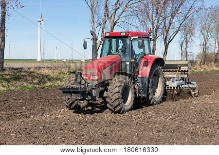 Red tractor plough at bare Dutch field in early springtime