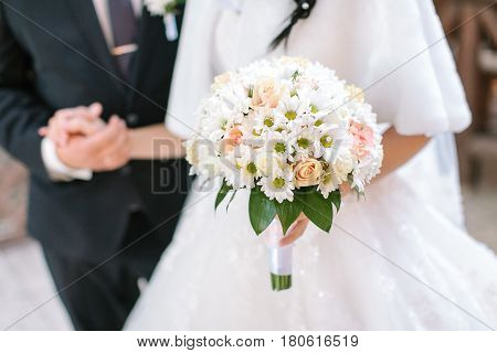 Wedding bouquet from fresh spring flowers. Bride holding white wedding bouquet close up. The groom holding by a hand the bride in a white wedding dress. marriage concept.