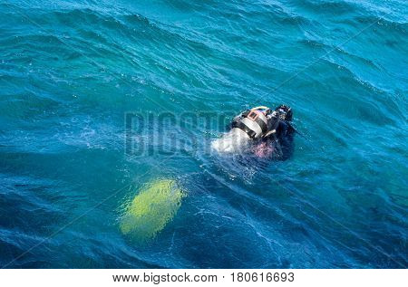 A scuba diver dives under the water in gear