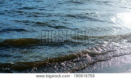 Sea waves on the beach dissolve in the rays of the sun. The marine nature of water. The idyllic scene of tranquility.