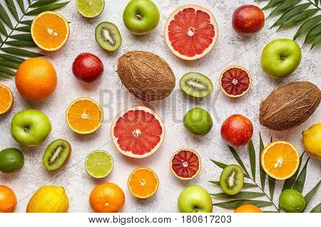 Organic fruit food background. Different citrus fruit, apple, kiwi and coconut on light background. Antioxidant, detox, dieting, clean eating, vegetarian vegan, healthy eating concept. Top view