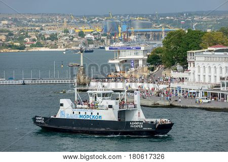 SEVASTOPOL, CRIMEA, RUSSIA - JULY 27: Summer sun is illuminating embankment of Artillery Bay and tourists on it near Monument to scuttled ships and on ferry boat on July 27, 2013 in Sevastopol, Crimea, Russia.
